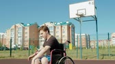 cadeira de rodas : Disabled man plays basketball from his wheelchair, On open air
