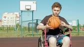 четыре человека : Disabled man plays basketball from his wheelchair, On open air
