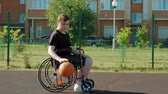 quatro pessoas : Disabled man plays basketball from his wheelchair, On open air