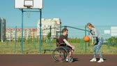 четыре человека : Disabled man plays basketball from his wheelchair With a woman, On open air, Make an effort when playing