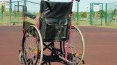 quatro pessoas : Type of wheelchair with a basket ball on a sports volleyball court