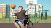 čtyři lidé : Disabled man plays basketball from his wheelchair, On open air, Make an effort when playing
