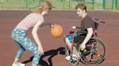 quatro pessoas : Disabled man plays basketball from his wheelchair With a woman, On open air, Make an effort when playing
