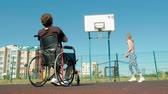 čtyři lidé : Disabled man plays basketball from his wheelchair With a woman, On open air, Make an effort when playing
