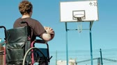cadeira de rodas : Disabled man plays basketball from his wheelchair With a woman, On open air, Make an effort when playing