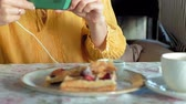 dish photo : Beautiful woman is eating waffles in cafe uses a smartphone to take a photo Stock Footage
