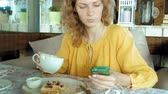 kaplar : Beautiful woman is eating waffles in cafe uses a smartphone to take a photo Stok Video