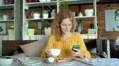 ifade : Beautiful woman is eating waffles in cafe uses a smartphone to take a photo Stok Video