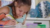 impresso : Creative girl using 3d pen printing 3D shape.