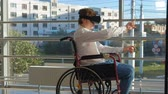 инвалид : disabled man on a wheelchair at a window uses a helmet of virtual reality