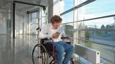 listening : disabled man on a wheelchair at a window listening to music on headphones from a smartphone