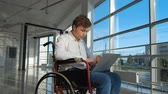 computador tablet : disabled businessman on a wheelchair at a window with a laptop