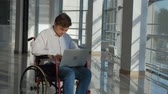 инвалид : disabled businessman on a wheelchair at a window with a laptop