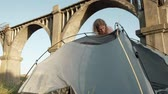 namiot : Young woman collects a tourist tent near the old bridge