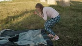 saco : Young woman collects a tourist tent near the old bridge