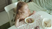 завтрак : Happy beautiful girl eating porridge for breakfast and having fun in white kitchen at home Стоковые видеозаписи