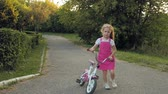 atlamacı : A happy, beautiful, little girl with long blond hair in a pink skirt and jumper rides a childrens bike on the road, she smiles. Super slow motion