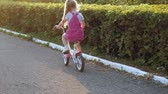 ciclismo : A happy, beautiful, little girl with long blond hair in a pink skirt and jumper rides a childrens bike on the road, she smiles. Super slow motion