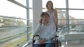 akik : Business woman wheeling a wheelchair with a disabled businessman on a wheelchair who is talking on the phone Stock mozgókép