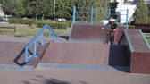 riders : A boy is riding BMX cycling tricks in a skateboard park on a sunny day. Super Slow Motion Stock Footage