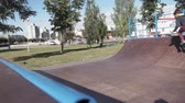 gençlik : A boy is riding BMX cycling tricks in a skateboard park on a sunny day. Super Slow Motion Stok Video