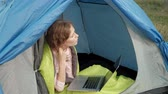 blogger : Young woman working behind a laptop in a tourist tent