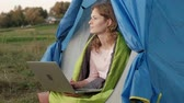 stan : Young woman working behind a laptop in a tourist tent