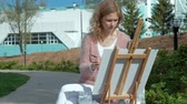ela : A pretty woman with red hair, paints a picture on canvas, which stands on the easel. The lady is in the open air near the lake of the river, she draws from life Stock Footage