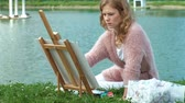 стенды : A pretty woman with red hair, paints a picture on canvas, which stands on the easel. The lady is in the open air near the lake of the river, she draws from life Стоковые видеозаписи
