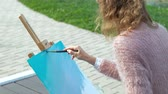 ressam : A pretty woman with red hair, paints a picture on canvas, which stands on the easel. The lady is in the open air near the lake of the river, she draws from life Stok Video