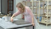 checker : The woman in the workshop is working on wooden boards, creating an effect of antiquity