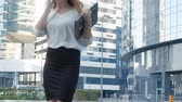 zaměřen : Young business woman talking is using smartphone in city park business center