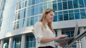 formal : Young businesswoman working on laptop in city park business center Stock Footage