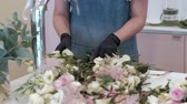 decorador : Florist prepares a bouquet of flowers for sale Stock Footage