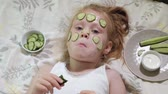 lánya : Little beautiful beautiful girl is making cucumber masks at home and eating vegetables
