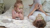 lánya : A woman with her daughter makes fun of cucumber masks at home
