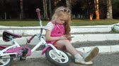 ugró : A little beautiful girl in a pink dress is sitting in the park on the steps and enjoys a smartphone in headphones, the bicycle is lying next to each other