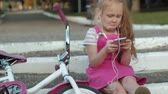 ela : A little beautiful girl in a pink dress is sitting in the park on the steps and enjoys a smartphone in headphones, the bicycle is lying next to each other
