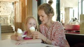 sní : A young mother and her little daughter spend time in a restaurant at a slow pace. Eating ice cream