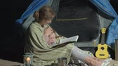 sní : Mother and her beautiful daughter read a book near a tourist tent at night on the beach