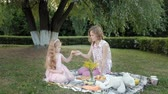lánya : A happy mother and daughter are drinking tea on the veil. Family in a city park on a picnic on a warm evening at sunset.