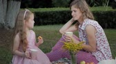 вуаль : A happy mother and daughter are drinking tea on the veil. Family in a city park on a picnic on a warm evening at sunset.