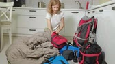 католицизм : A woman tourist collects things in a backpack in the kitchen of the house and prepares for a trip