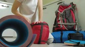 catolicismo : A woman tourist collects things in a backpack in the kitchen of the house and prepares for a trip