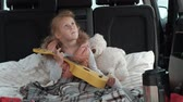 lánya : Beautiful little girl sitting in an open trunk of a car on the river bank of the sea playing on a yellow ukulele