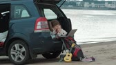 erhängen : Beautiful young woman and her little daughter are sitting in the open trunk of a car on the river bank of the sea enjoying a laptop