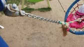 playground : A little girl in a pink dress swings on a round swing in the playground