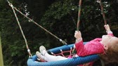 dětské hřiště : A little girl in a pink dress swings on a round swing in the playground