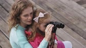lánya : A woman with her daughter looking through binoculars on the beach