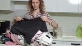 sprzataczka : woman ironing a mountain of laundry at home in the kitchen